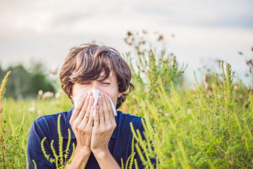Jongeman niesend in een veld met veel pollen